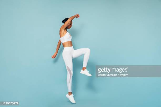 full length of woman exercising against blue background - sportswear stock pictures, royalty-free photos & images