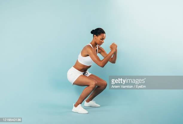 full length of woman exercising against blue background - crouching stock pictures, royalty-free photos & images