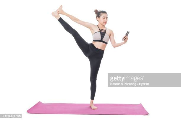 full length of woman exercising against white background - エクササイズマット ストックフォトと画像