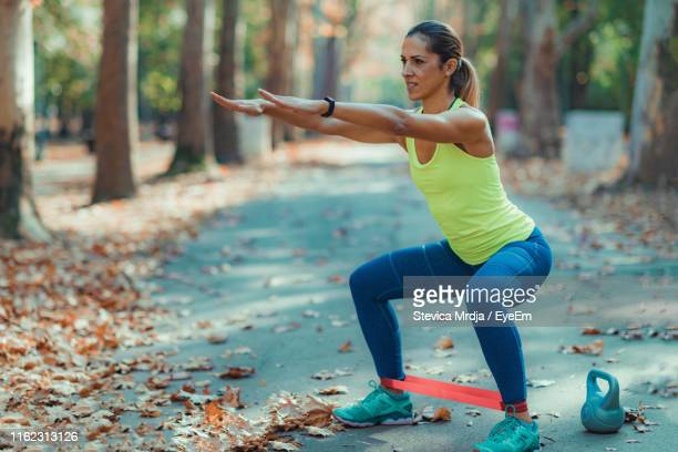 full length of woman exercising at park during autumn - mid adult women stock pictures, royalty-free photos & images