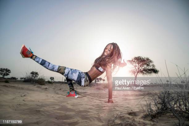 full length of woman exercising in desert against clear sky during sunset - one mid adult woman only stock pictures, royalty-free photos & images