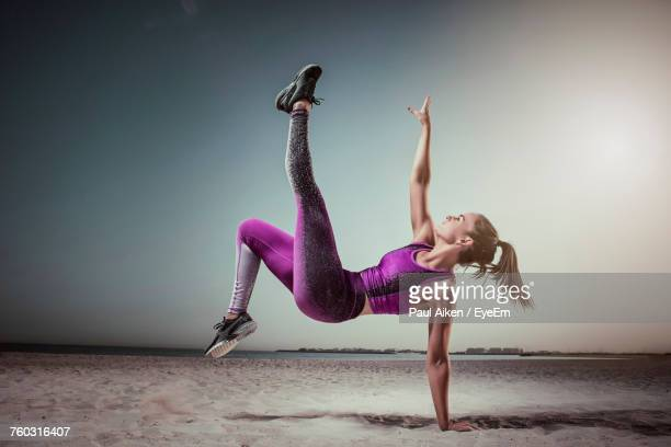 full length of woman exercising on beach - aikāne stock pictures, royalty-free photos & images
