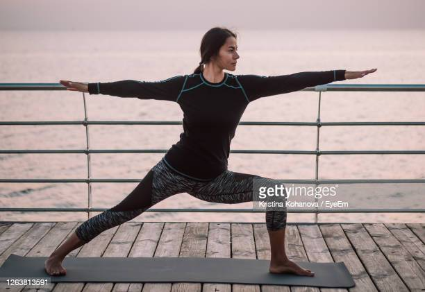 full length of woman exercising on footbridge - legs apart stock pictures, royalty-free photos & images