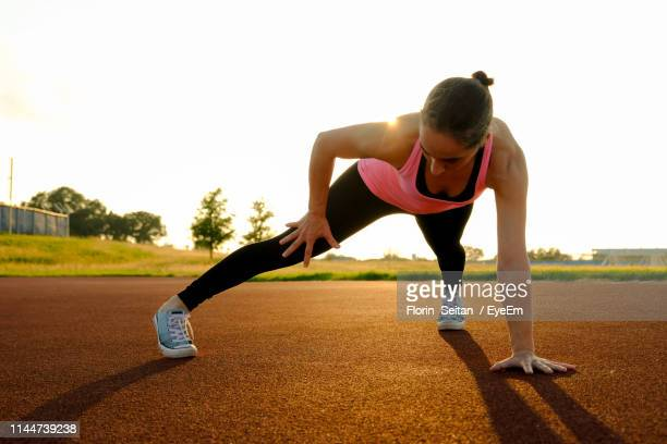full length of woman exercising on road against sky during sunset - florin seitan stock pictures, royalty-free photos & images