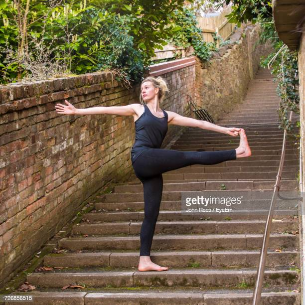 Full Length Of Woman Exercising While Standing On Steps