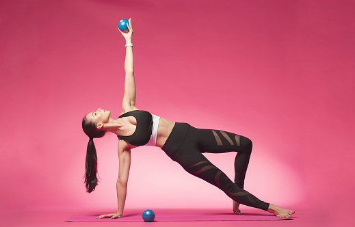 Full Length Of Woman Exercising With Pilates Balls On Pink Background - gettyimageskorea