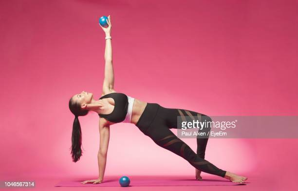 full length of woman exercising with pilates balls on pink background - pilates stock pictures, royalty-free photos & images