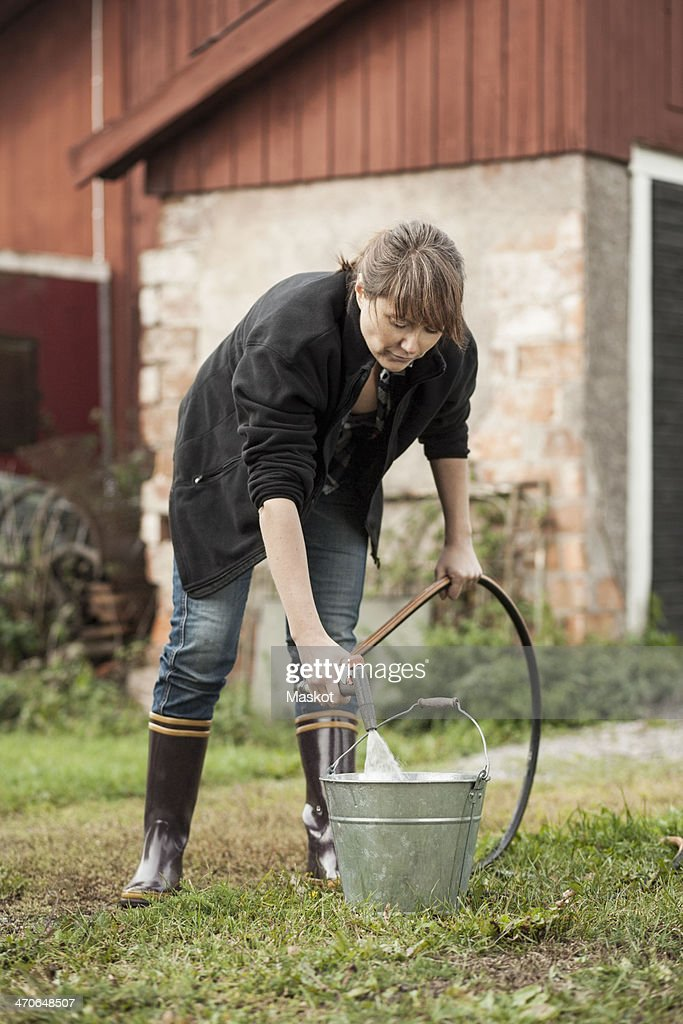 Full length of woman filling water with hose at farm : Stock Photo