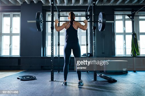 Full length of woman gripping barbell in gym