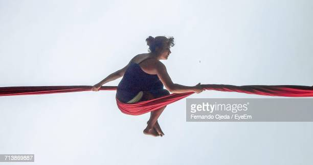 Full Length Of Woman Hanging On Red Silk Against Sky