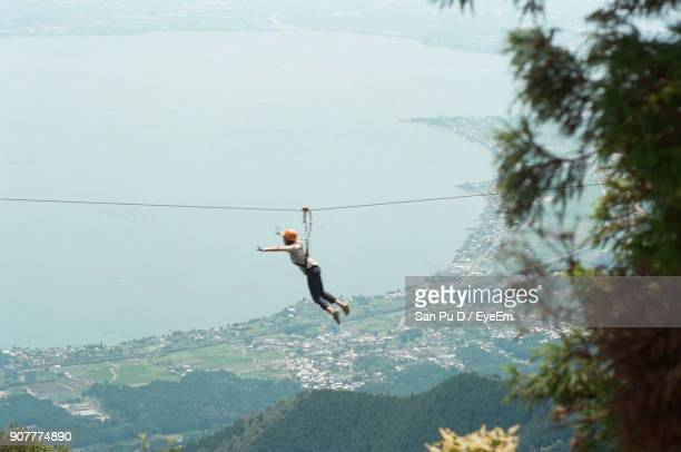 Full Length Of Woman Hanging On Rope