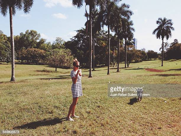 Full Length Of Woman Having Drink While Standing On Grassy Field With Dog