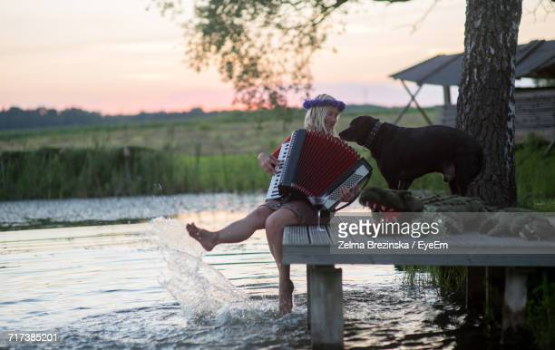 Full Length Of Woman Holding Accordion With Dog And Crocodile Toy On Table By Lake