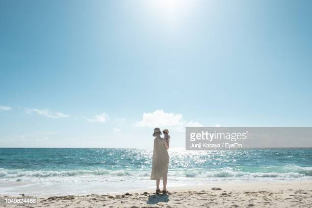 full length of woman holding baby while standing on beach against sky - horizont über wasser stock-fotos und bilder