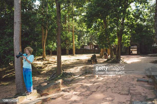 full length of woman holding camera while standing by trees - bortes photos et images de collection