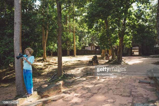 full length of woman holding camera while standing by trees - bortes fotografías e imágenes de stock