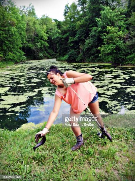 full length of woman holding fish by pond - baum stock pictures, royalty-free photos & images