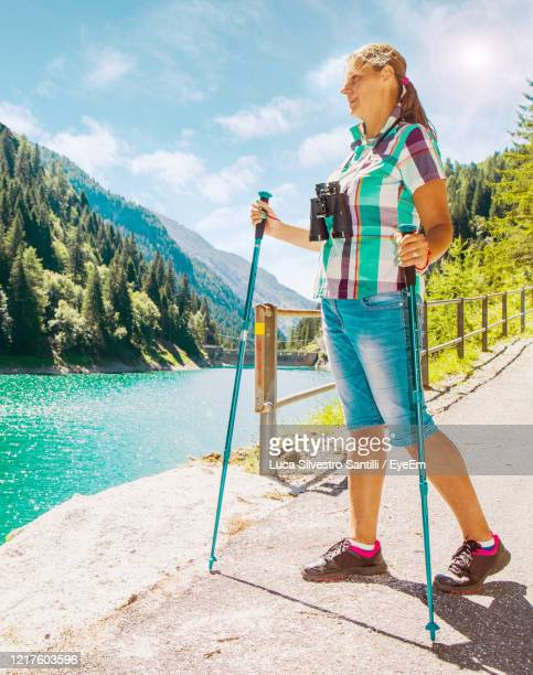 full length of woman holding hiking poles while standing on footpath - hiking pole stock pictures, royalty-free photos & images