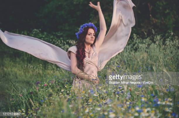 full length of woman holding purple flowers on field - bogdan negoita stock pictures, royalty-free photos & images