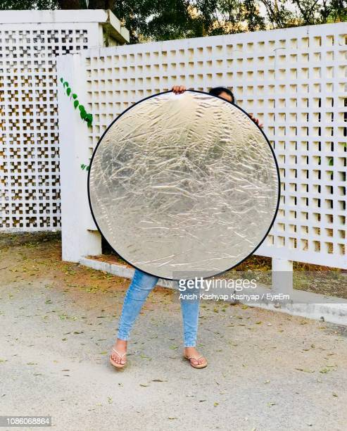full length of woman holding reflector against fence - リフレクター ストックフォトと画像