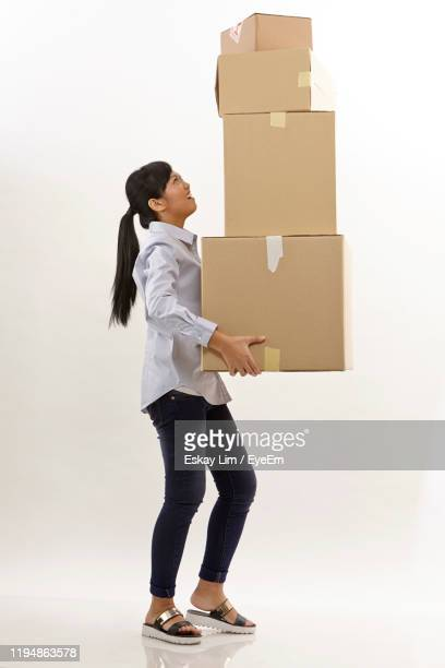full length of woman holding stacked cardboard box over white background - carrying stock pictures, royalty-free photos & images