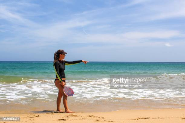 Full Length Of Woman Holding Tennis Racket While Pointing At Beach Against Sky