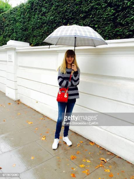 Full Length Of Woman Holding Umbrella While Standing On Footpath