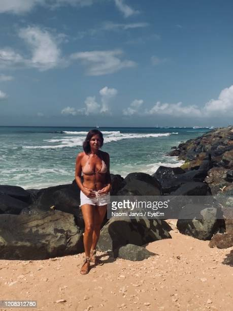 full length of woman in bikini standing on beach - naomi jarvis stock pictures, royalty-free photos & images