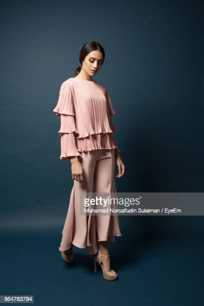 full length of woman in casuals standing against gray background - manches longues photos et images de collection