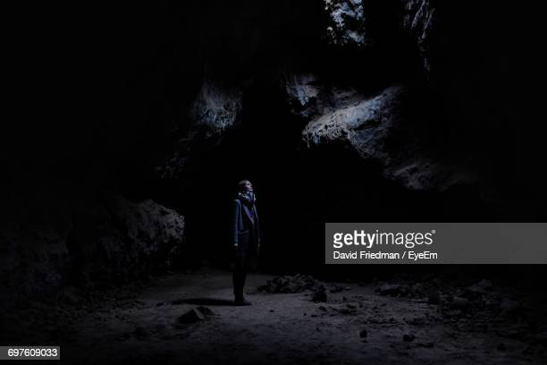 full length of woman in cave - cave stock pictures, royalty-free photos & images