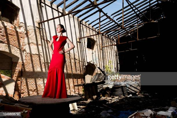 full length of woman in dress standing on table in abandoned building - evening gown stock pictures, royalty-free photos & images