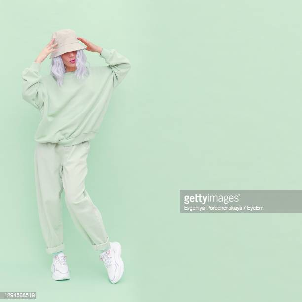 full length of woman in hat standing against colored background - pink pants stock pictures, royalty-free photos & images