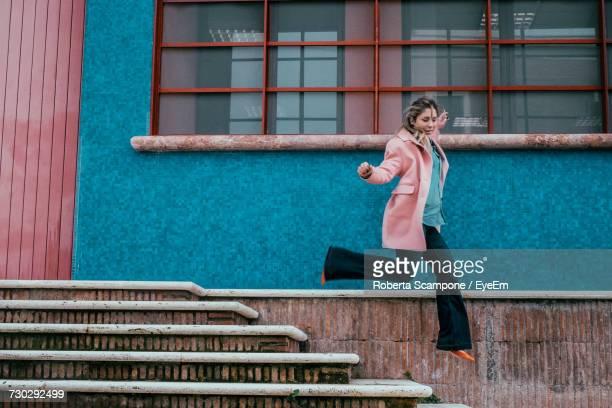 Full Length Of Woman In Mid-Air Jumping Over Steps By House