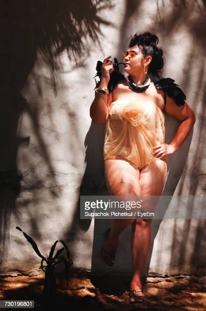 Full Length Of Woman In Nightie Smoking Pipe While Leaning On Wall