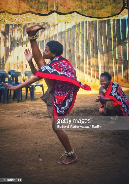full length of woman in traditional clothing dancing outdoors - swaziland fotografías e imágenes de stock