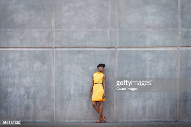 full length of woman in yellow dress standing against wall - vestido amarillo fotografías e imágenes de stock