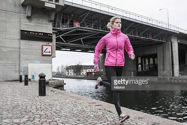 full length of woman jogging against bridge - 運河 ストックフォトと画像
