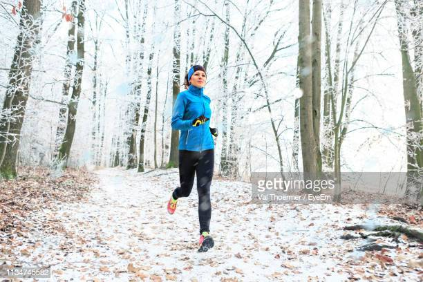 full length of woman jogging in forest during winter - val thoermer stock-fotos und bilder
