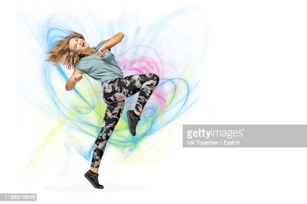 full length of woman jumping against abstract background - bearbeitungstechnik stock-fotos und bilder