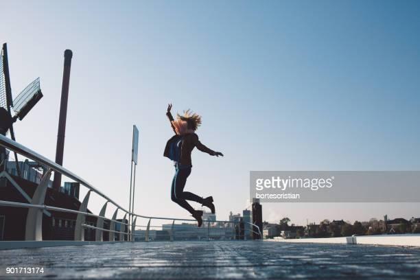 full length of woman jumping against clear sky - bortes fotografías e imágenes de stock