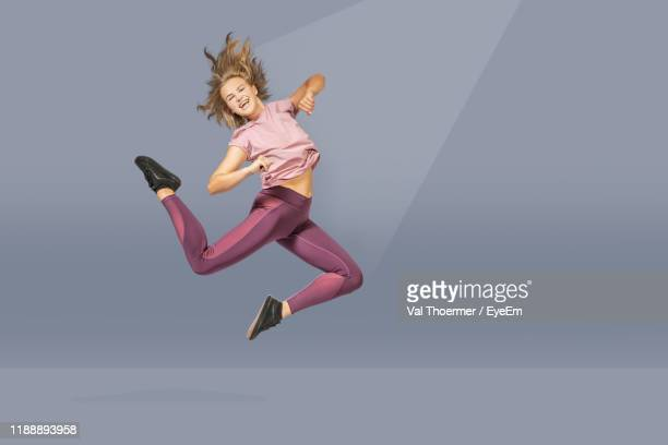 full length of woman jumping against gray background - val thoermer stock-fotos und bilder