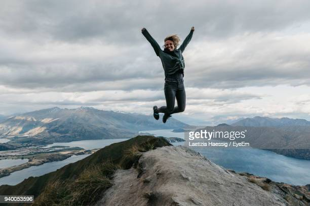 Full Length Of Woman Jumping On Cliff