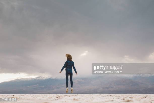 full length of woman jumping on field against sky - adults only stock pictures, royalty-free photos & images