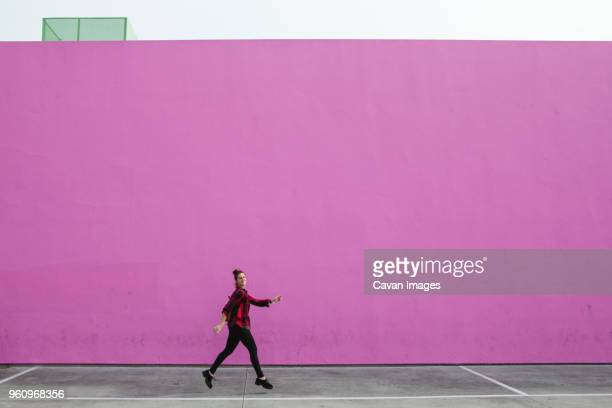 full length of woman jumping on footpath against pink wall - los angeles città foto e immagini stock