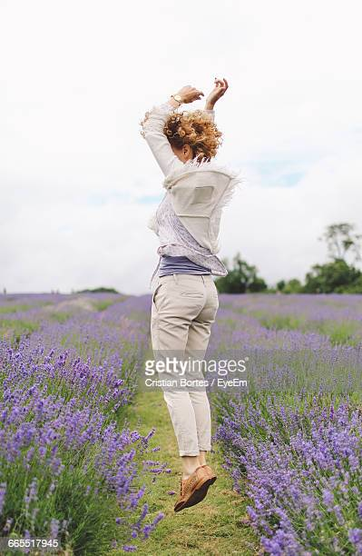 Full Length Of Woman Jumping On Lavender Field