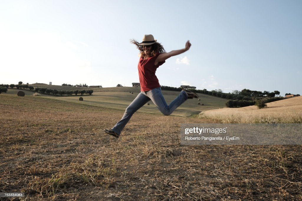 Full Length Of Woman Jumping Over Field Against Sky : Stock Photo