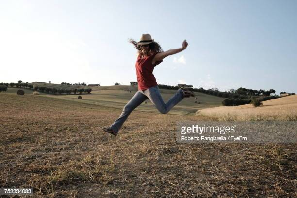 Full Length Of Woman Jumping Over Field Against Sky