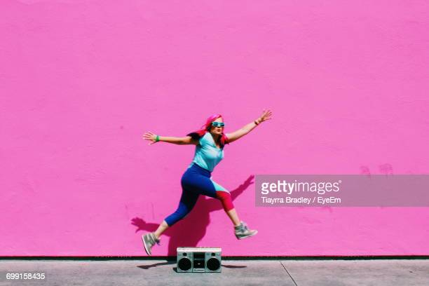 Full Length Of Woman Jumping Over Old-Fashioned Radio Against Pink Wall