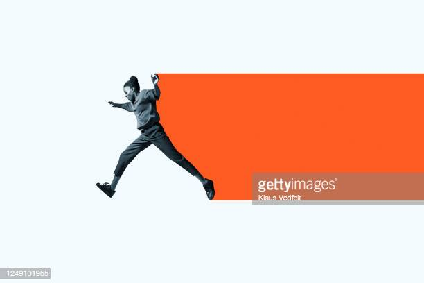 full length of woman jumping with orange trail - in movimento foto e immagini stock