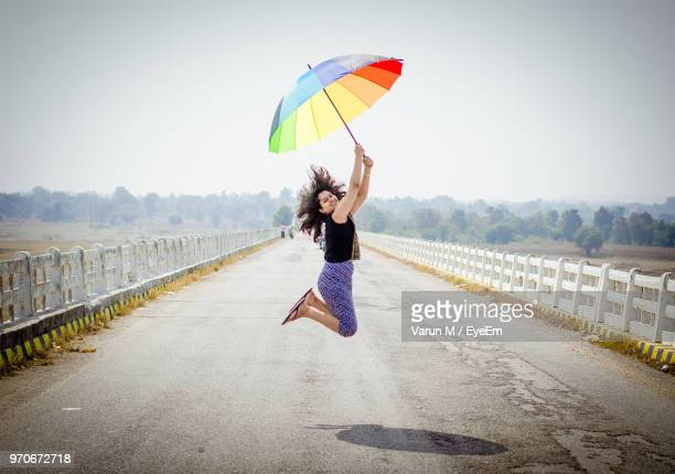 Full Length Of Woman Jumping With Umbrella On Road Against Clear Sky